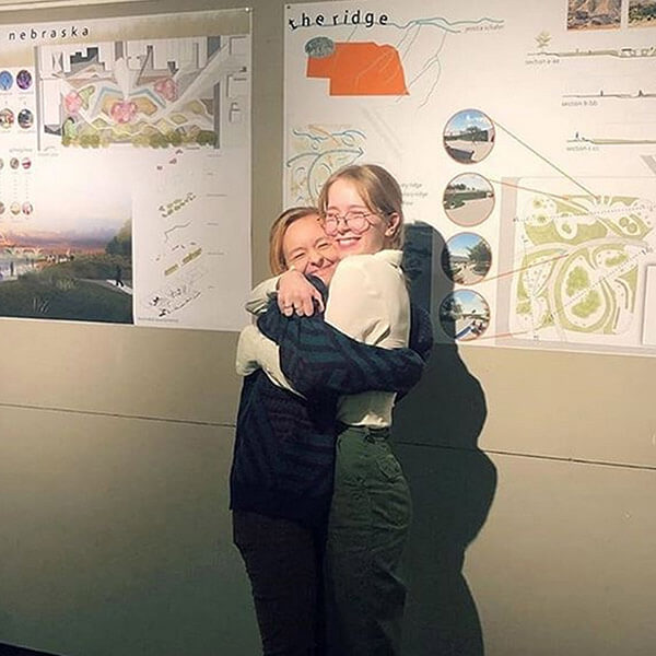 Students hug in front of presentation