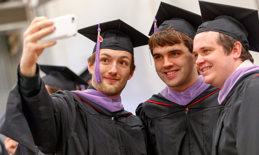 Students taking selfie in graduation robes