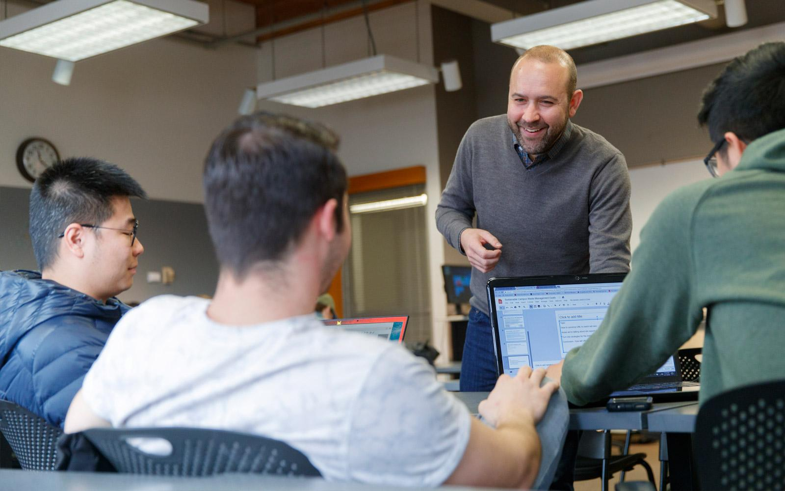 Faculty talks to students working on laptops